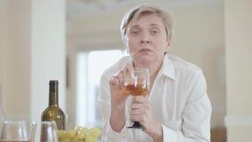 Retrato de la mujer mayor triste en la blusa blanca con los ojos azules que miran in camera que sostienen la copa de vino a dispo almacen de video