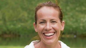 Retrato de la mujer de mediana edad sonriente en parque almacen de metraje de vídeo