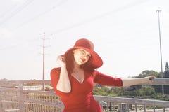 Retrato de la mujer de la moda en vestido y sombrero rojos en el puente Imagen de archivo