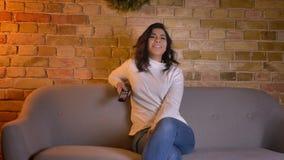 Retrato de la mujer morena caucásica alegre que se sienta en el sofá y la película de observación risueñamente en atmósfera caser almacen de video