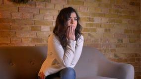 Retrato de la mujer morena caucásica emocional que se sienta en la novela de suspense de observación del sofá con la preocupación metrajes