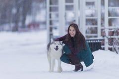 Retrato de la mujer morena caucásica positiva feliz que presenta con Husky Dog Outdoors Imagen de archivo