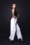 Retrato de la mujer morena hermosa en una blusa negra y pantalones blancos, Tiro de la foto de la moda Fotografía de archivo libre de regalías