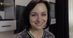 Retrato de la mujer morena joven cauc?sica bonita que sonr?e en casa almacen de metraje de vídeo