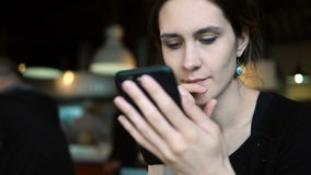 Retrato de la mujer morena joven que se sienta en café y que usa el smartphone para practicar surf las tiendas en línea de Intern metrajes
