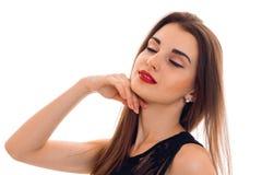 Retrato de la mujer morena joven sensual en el vestido negro elegante que presenta con los ojos cerrados aislados en el fondo bla fotos de archivo