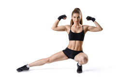 Retrato de la mujer muscular fuerte que dobla su bíceps y que estira la pierna Muchacha de la aptitud del recorte fotos de archivo