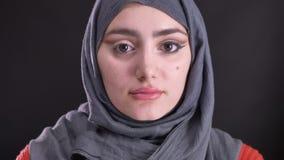 Retrato de la mujer musulmán atractiva en hijab con una ojo-flecha que da vuelta a su cabeza que muestra maquillaje a la cámara e almacen de metraje de vídeo
