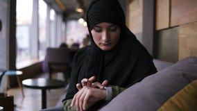 Retrato de la mujer musulmán en el hijab negro que se sienta en café moderno solamente y que usa sus relojes elegantes, golpe fue metrajes