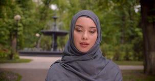 Retrato de la mujer musulmán en hijab que mira seriamente en la cámara que se coloca delante de la fuente almacen de video
