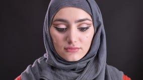 Retrato de la mujer musulmán hermosa en hijab con los relojes de moda del maquillaje modesto en cámara en fondo negro metrajes