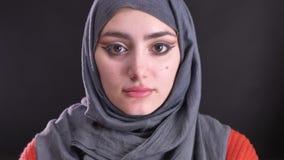 Retrato de la mujer musulmán hermosa en hijab con maquillaje brillante que mira seriamente en cámara en fondo negro metrajes