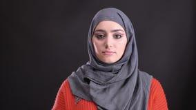 Retrato de la mujer musulmán hermosa en hijab con maquillaje brillante y brillante que mira tranquilamente en cámara en negro almacen de video