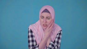 Retrato de la mujer musulmán hermosa joven que experimenta dolor de muelas severo almacen de metraje de vídeo