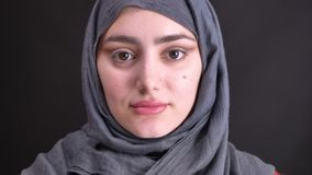 Retrato de la mujer musulmán joven en hijab con maquillaje a medio terminar que mira tranquilamente in camera en fondo negro almacen de video