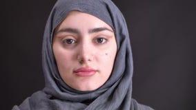 Retrato de la mujer musulmán joven en hijab que mira tranquilamente in camera en fondo negro metrajes