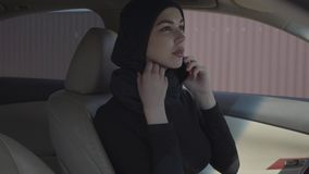Retrato de la mujer musulmán joven independiente que se sienta en su coche lookiing a sí misma en mirrir y que habla por almacen de video