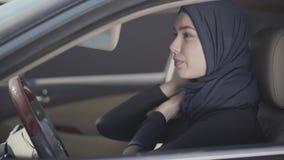 Retrato de la mujer musulmán joven independiente que se sienta en su coche y que corrige el pañuelo tradicional con la ayuda del  almacen de video