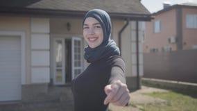 Retrato de la mujer musulmán joven independiente que sonríe y que liga el pañuelo tradicional que lleva en el fondo de la casa almacen de video