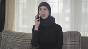 Retrato de la mujer musulmán joven seria independiente que habla por el smartphone que lleva el pañuelo tradicional metrajes