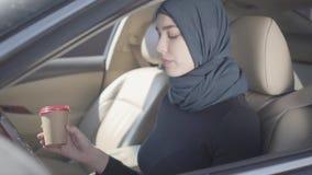 Retrato de la mujer musulmán joven sonriente independiente que se sienta en el coche, café de consumición y hablando llevando del metrajes