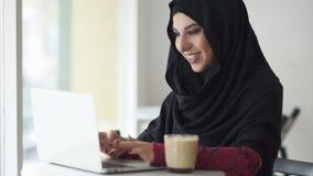 Retrato de la mujer musulmán joven sonriente que trabaja en el ordenador portátil moderno en café y capuchino de consumición Muje almacen de metraje de vídeo