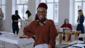 Retrato de la mujer de negocios africana joven del empresario, trabajador creativo en lentes que sonríe en la oficina ligera mode metrajes