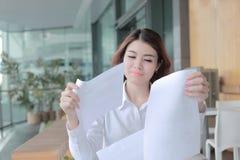 Retrato de la mujer de negocios asiática joven hermosa que lleva a cabo cartas o papeleo en su mano en el escritorio en oficina Foto de archivo libre de regalías