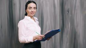 Retrato de la mujer de negocios en fondo gris