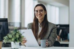 Retrato de la mujer de negocios joven bonita sonriente en los vidrios que se sientan en lugar de trabajo y que trabajan con los d fotografía de archivo
