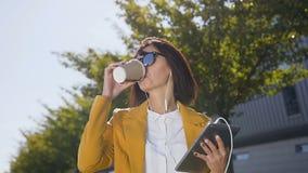 Retrato de la mujer de negocios joven caucásica usando la tableta mientras que soportes cerca del centro de la oficina outdoors M almacen de metraje de vídeo