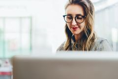 Retrato de la mujer de negocios joven en los vidrios de moda que se sientan en café, trabajando en el ordenador portátil El Blogg imagen de archivo libre de regalías