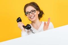 Retrato de la mujer de negocios joven feliz sonriente emocionada hermosa confiada con el teléfono que muestra la cartelera en bla foto de archivo libre de regalías