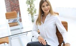 Retrato de la mujer de negocios moderna que se sienta en una silla Imagen de archivo