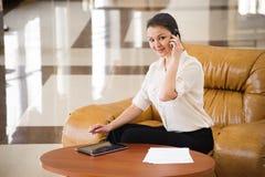 Retrato de la mujer de negocios ocupada que trabaja en ipad mientras que se sienta en el sofá Pequeña empresa imágenes de archivo libres de regalías
