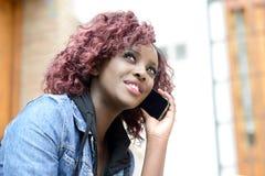 Mujer negra hermosa en fondo urbano en el teléfono Foto de archivo libre de regalías