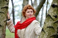 Retrato de la mujer orgullosa con una bufanda roja entre abedules Imágenes de archivo libres de regalías