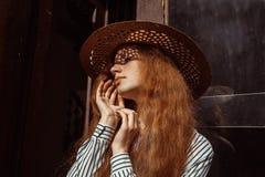 Retrato de la mujer pelirroja hermosa en sombrero de paja con la sombra Fotografía de archivo