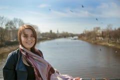 Retrato de la mujer positiva joven en el puente contra pájaros del cielo azul y del río El concepto ilustra tiempo de primavera d Fotos de archivo