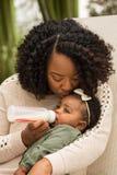 Retrato de la mujer que alimenta a su hija con una botella Fotografía de archivo