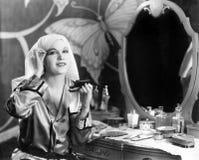 Retrato de la mujer que aplica maquillaje en el tocador (todas las personas representadas no son vivas más largo y ningún estado  foto de archivo libre de regalías