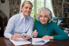 Retrato de la mujer que ayuda al vecino mayor con papeleo imagen de archivo
