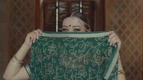 Retrato de la mujer que liga, cubriendo la cara con la sari metrajes
