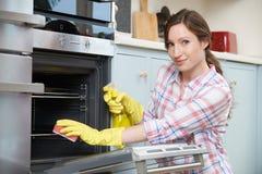 Retrato de la mujer que limpia a Oven At Home Imagen de archivo libre de regalías