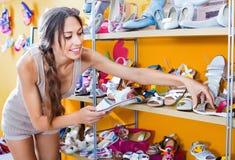 Retrato de la mujer que mira confundido con dos pares de zapatos Fotos de archivo libres de regalías