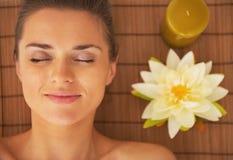 Retrato de la mujer que pone en la tabla del masaje lista para la terapia del balneario Imagenes de archivo