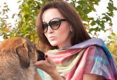 Retrato de la mujer que se coloca en el parque con el perro Imágenes de archivo libres de regalías