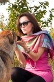Retrato de la mujer que se coloca en el parque con el perro Imagen de archivo