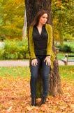 Retrato de la mujer que se coloca en el parque en otoño Foto de archivo