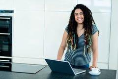 Retrato de la mujer que se inclina en worktop con el ordenador portátil y la taza de té en frente Imagenes de archivo